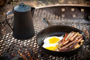 Coffee, eggs and sausage breakfast cooking over a campfire. Cast iron fry pan and coffee pot are on a steel grate placed directly over the flame and coals. No people in photo. High resolution color photograph. Horizontal composition.
